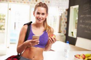 Woman Wearing Gym Clothing Choosing Fruit From Bowl